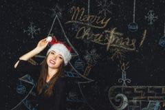 一个少妇的画象圣诞老人盖帽的圣诞节背景的 图库摄影