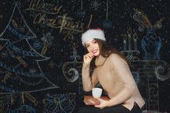 一个少妇的画象圣诞老人盖帽的圣诞节背景的 免版税库存图片
