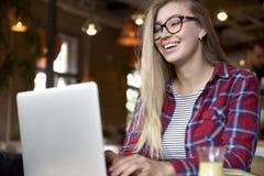 一个少妇的画象戴长的头发和眼镜的在桌上 免版税库存照片