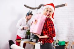 一个少妇的画象有一桃红色giftbox的在家在前景 圣诞老人帽子的美丽的金发碧眼的女人,在a的红色衬衣 免版税库存图片
