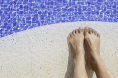 一个少妇的脚在水池边缘的 免版税库存照片