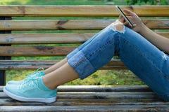一个少妇的腿牛仔裤的在一条长凳在公园 库存照片