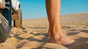 一个少妇的腿的特写镜头在4x4汽车车旁边的享受在一个的日落沙漠沙丘 免版税库存图片