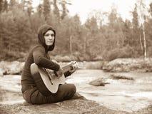 一个少妇的被定调子的图象有吉他的 免版税库存图片