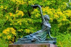 一个少妇的雕塑有一张手帕的在他们的手上在秋天公园 免版税库存图片