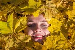 一个少妇的面孔有一个美丽的女孩嘴唇的有在aut的黄色槭树叶子在的红色唇膏和被绘的鞭子的 免版税库存图片