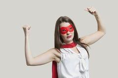 一个少妇的画象屈曲在灰色背景的特级英雄服装的肌肉 库存图片