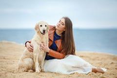 一个少妇的画象有一条狗的在海滩 免版税库存图片