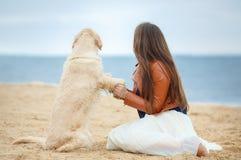 一个少妇的画象有一条狗的在海滩 免版税库存照片
