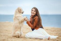 一个少妇的画象有一条狗的在海滩 库存图片