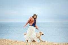 一个少妇的画象有一条狗的在海滩 库存照片