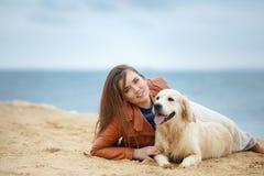 一个少妇的画象有一条狗的在海滩 图库摄影