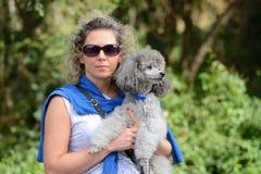 一个少妇的画象有一条长卷毛狗的在手上 库存照片