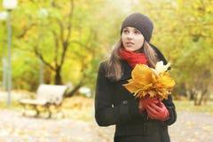 一个少妇的画象有下落的叶子的 免版税库存照片