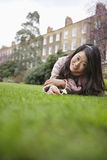 一个少妇的画象有花说谎的草坪的在大厦前面 免版税库存图片