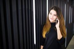 一个少妇的画象谈话在手机对现代办公室墙壁 免版税库存照片
