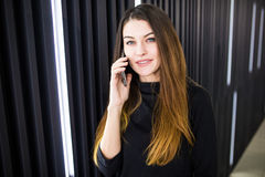 一个少妇的画象谈话在手机对现代办公室墙壁 库存照片