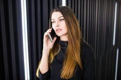 一个少妇的画象谈话在手机对现代办公室墙壁 免版税图库摄影