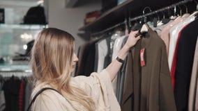 一个少妇看在精品店的一个挂衣架垂悬的衣裳 影视素材