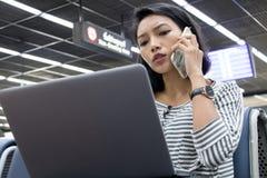 一个少妇研究一台计算机在机场 免版税库存图片