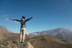 一个少妇背包徒步旅行者的掌声在一个蔓延的向上山峰顶部的 自由和胜利反对 免版税库存照片