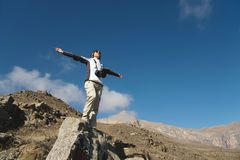 一个少妇背包徒步旅行者的掌声在一个蔓延的向上山峰顶部的 自由和胜利反对 免版税库存图片