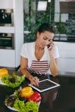 一个少妇花费时间在家,在厨房和roo的 库存照片
