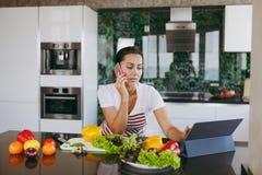 一个少妇花费时间在家,在厨房和roo的 库存图片
