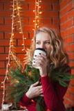 一个少妇装饰一个房子圣诞节和新年 喝cofee 以砖墙为背景 免版税库存照片