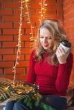 一个少妇装饰一个房子圣诞节和新年 喝cofee 以砖墙为背景 库存图片