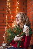 一个少妇装饰一个房子圣诞节和新年 喝cofee 以砖墙为背景 库存照片