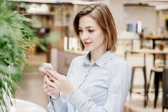 一个少妇谈话通过电话 女孩坐在桌上并且做命令 2 business woman 库存照片