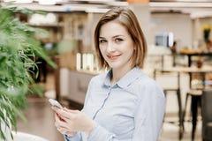一个少妇谈话通过电话 女孩坐在桌上并且做命令 2 business woman 免版税库存图片