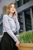 一个少妇谈话通过电话 女孩坐在桌上并且做命令 2 business woman 库存图片
