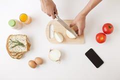 一个少妇连接的互联网和烹调每日早餐  库存图片