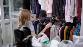 一个少妇选择在一个时兴的精品店的衣裳,夫人审查在挂衣架称的毛线衣 股票录像
