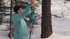 一个少妇通过冬天森林走并且采取在她的电话的一selfie 影视素材