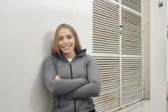 一个少妇,倾斜在白色墙壁,体育穿衣 库存图片