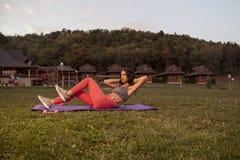 一个少妇,健身,吸收,增加锻炼席子,户外, e 免版税库存图片