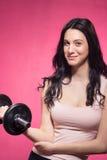 一个少妇,哑铃衡量举行,桃红色背景 库存图片