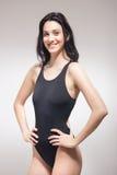 一个少妇,微笑的愉快的游泳者泳装 免版税图库摄影