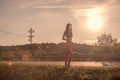 一个少妇,户外跑步,体育穿衣,太阳天空,温暖 免版税库存照片