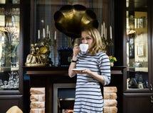一个少妇stends的画象在壁炉附近的,愉快的微笑的女孩喝茶 图库摄影
