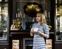 一个少妇stends的画象在壁炉附近的,愉快的微笑的女孩喝茶 库存图片