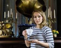 一个少妇stends的画象在壁炉附近的,愉快的微笑的女孩喝茶 免版税图库摄影