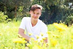 一个少年年轻男孩获得乐趣在菊花的领域 免版税库存照片