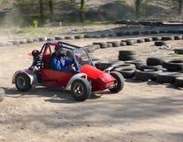 一个少年的种族children&的x27; 沿沙子轨道的s儿童车 免版税库存照片