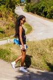 一个少年黑人女孩的室外画象有蓝色longboard ska的 免版税库存照片