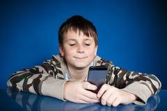一个少年的画象有电话的 免版税库存照片