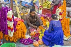 一个尼泊尔人卖花给一件蓝色礼服的一名妇女,摊贩明亮五颜六色新鲜 免版税库存图片